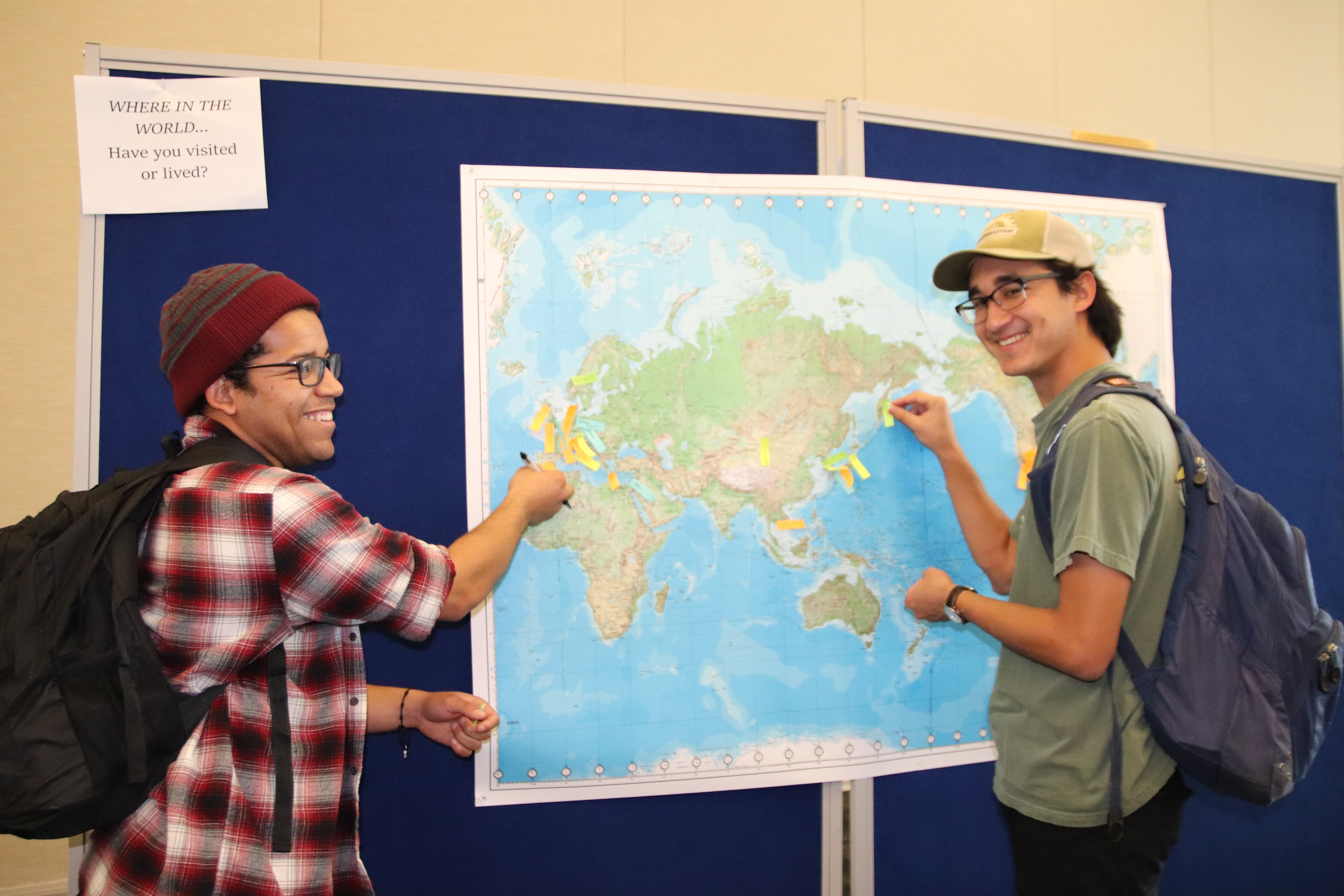 Students pinpointing parts of the world they have visited or lived on a map of the Earth.