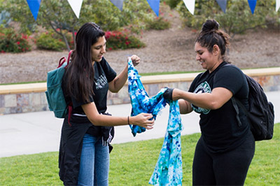 Two students apply dye to t-shirts