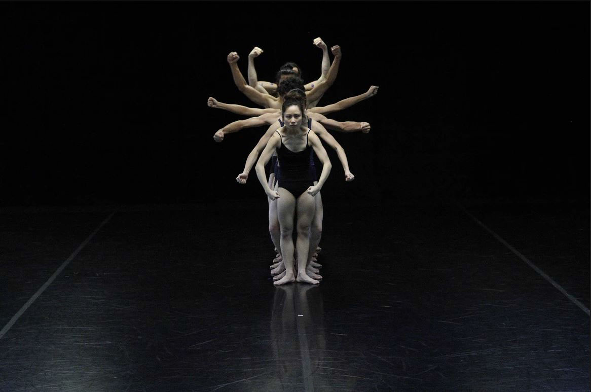 Dancers in pose on a dark stage